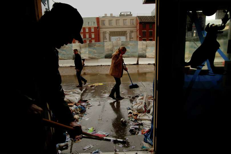 Robert Zink, left, and Amanda Zink, center, start to clean up their store