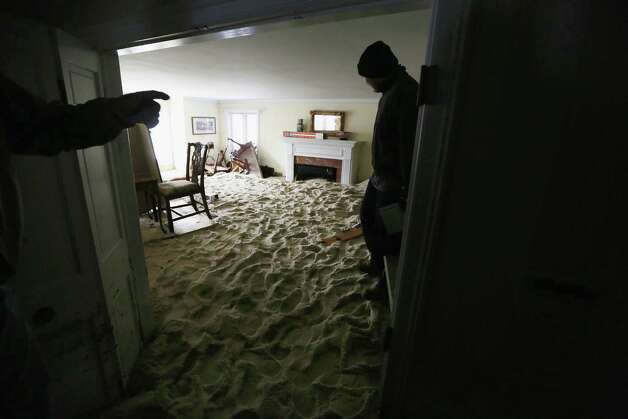 A worker stands in a living room filled with sand washed in by Superstorm Sandy on November 14, 2012 in Bay Head, New Jersey. Many residents of the hard hit seaside town remain without power following Superstorm Sandy. Photo: Mario Tama, Getty Images / 2012 Getty Images