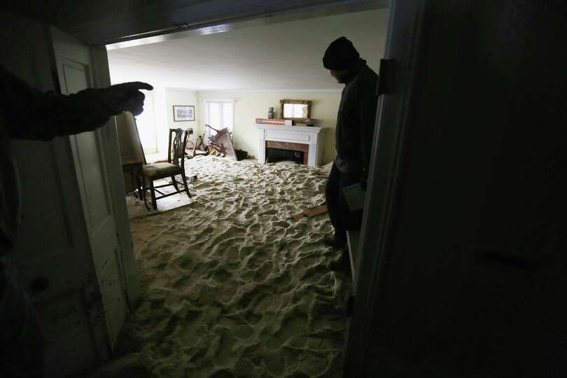 A worker stands in a living room filled with sand washed in by Superstorm Sandy on November 14, 2012