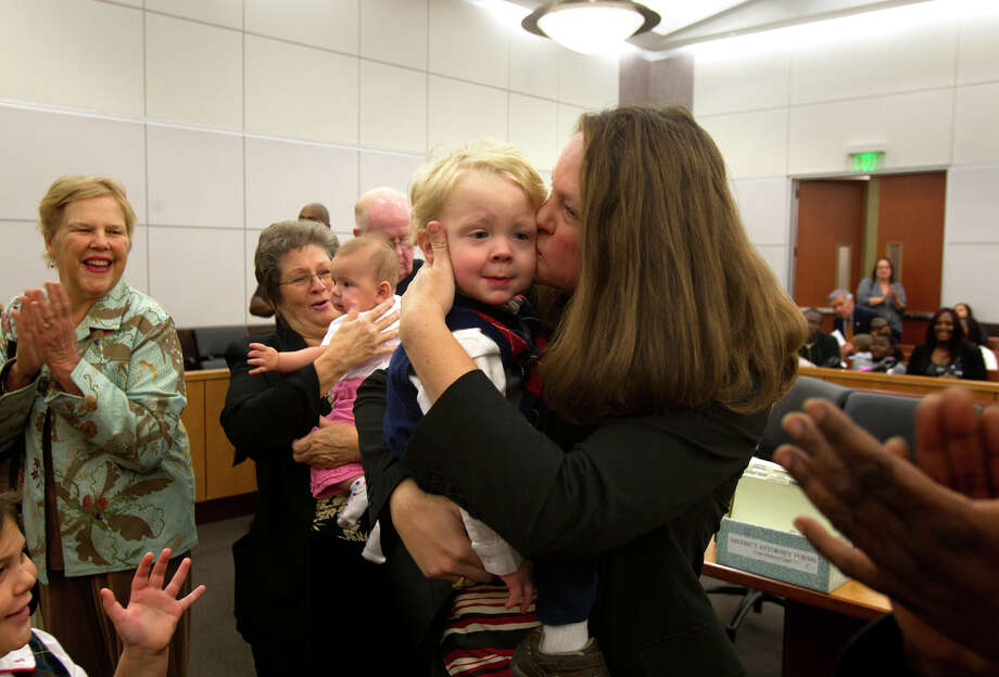"Family watches as Anne Marie Walsh kisses her newly adopted son, Aidan Walsh, 2, in the courtroom during a mass adoption at the Juvenile Justice Center Friday, Nov. 16, 2012, in Houston. Over 70 Child Protective Services children were adopted during the event. ""We'll all be thankful for the blessings we've been given this year,"" Walsh said. Photo: Cody Duty, Houston Chronicle / © 2012 Houston Chronicle"