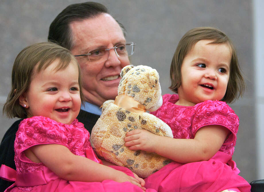 Keith Simpson holds his newly adopted 20-month-old twin sisters Emma and Bethany, right, and David, 3, not pictured, during a mass adoption at the Juvenile Justice Center Friday, Nov. 16, 2012, in Houston. Photo: Cody Duty, Houston Chronicle / © 2012 Houston Chronicle