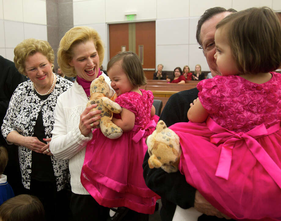 "Pat Ware watches as her daughter Lisa Simpson smiles after she and her husband Keith Simpson, right, adopted 20-month-old twin sisters Bethany and Emma, right, and David, 3, not pictured, during a mass adoption at the Juvenile Justice Center Friday, Nov. 16, 2012, in Houston. ""Our family is finally complete,"" Lisa said. Photo: Cody Duty, Houston Chronicle / © 2012 Houston Chronicle"