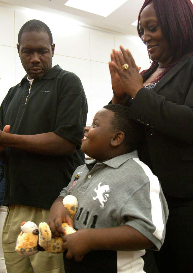Gerald Johnson, left and LaSonya King-Johnson, right, look at Richard King-Johnson, 7, after they adopted him during a mass adoption event at the Juvenile Justice Center Friday, Nov. 16, 2012, in Houston. Over 70 Child Protective Services children were adopted during the event. Photo: Cody Duty, Houston Chronicle / © 2012 Houston Chronicle
