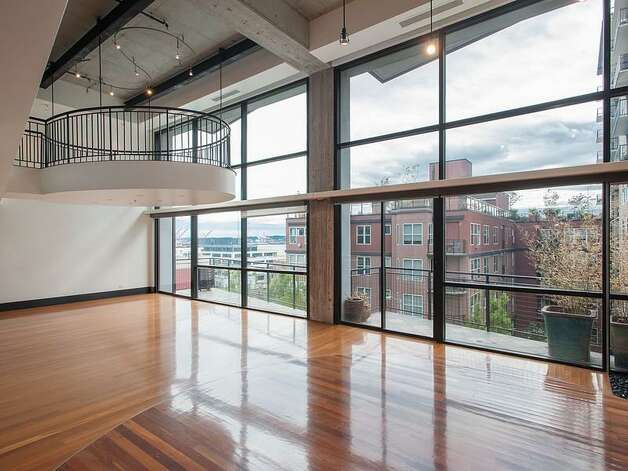 Banner Building: This Belltown loft, designed by Ed Weinstein, is 3,700 square feet on two floors, with dramatic two-story windows and a floating balcony. Photo: Courtesy Realogics Sotheby's International Realty