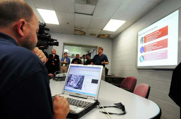 Greg Dixon, left, sales support manager for ShotSpotter technology, operates the computer software for the system, as Gregg Rowland, Senior V.P.of ShotSpotter, right, explains the system to members of the Troy Police Department, Sept. 3, 2008, in Troy, N.Y. (James Goolsby / Times Union archive) Photo: JAMES GOOLSBY JAMES GOOLSBY / 00000109A