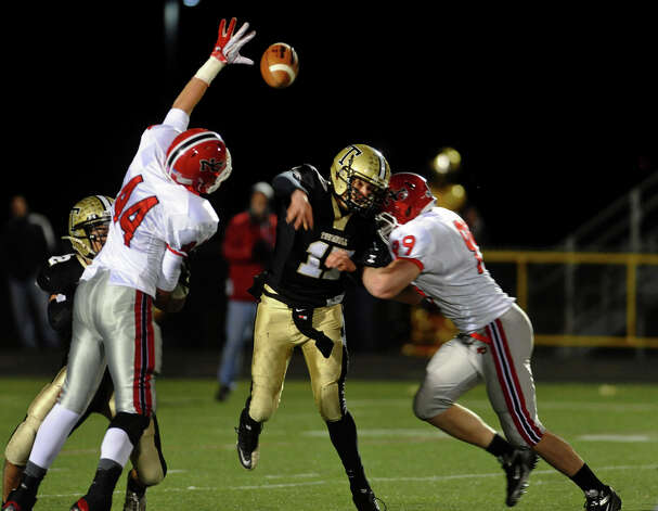 Trumbull QB Nick Roberts throws a pass as New Canaan's #99 Connor Buck looks to sack and teammate #44 Zachary Allen tries to block, during boys football action in Trumbull, Conn. on Friday November 16, 2012. Photo: Christian Abraham / Connecticut Post
