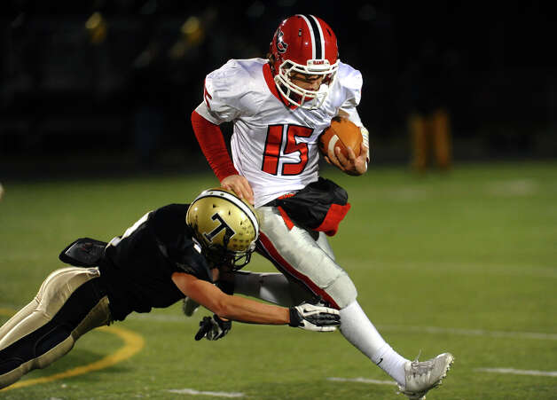 New Canaan QB Nick Cascione tries to avoid a tackle by Trumbull's #7 Thomas Hayduk, during boys football action in Trumbull, Conn. on Friday November 16, 2012. Photo: Christian Abraham / Connecticut Post