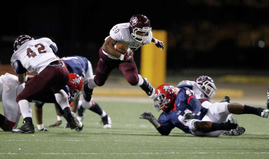 Cy-Fair's (#20) Dillon Birden jumps over Alief Taylor players in the first half of the Class 5A Division I Playoff Football game at Berry Center on Friday, Nov. 16, 2012, in Houston. Photo: Mayra Beltran, Houston Chronicle / © 2012 Houston Chronicle