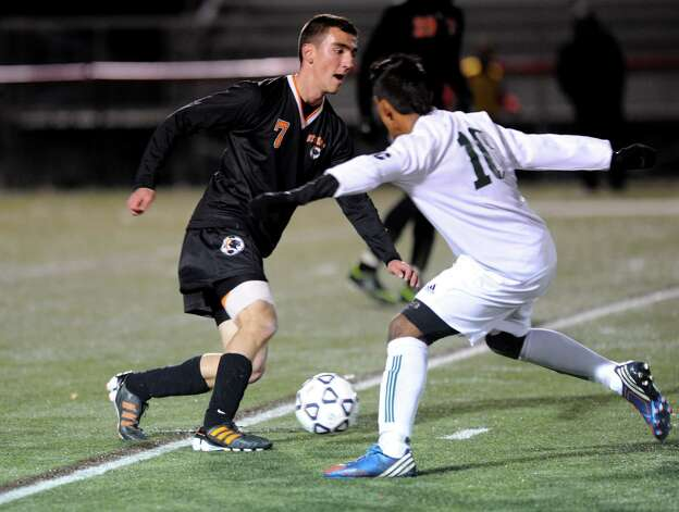 Stamford's Lucas Laria and Norwalk's Santiago Muriel compete for control of the ball during Friday's Class LL boys soccer semifinal game at New Canaan High School on November 16, 2012. Photo: Lindsay Niegelberg / Stamford Advocate