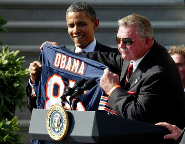 "FILE - In this Oct. 7,2011 file photo, former Chicago Bears head football coach Mike Ditka presents President Barack Obama with a jersey as the 1985 Super Bowl XX Champions Chicago Bears football team are honored on the South Lawn of  the White House in Washington. In a rare show of unity, President Barack Obama and challenger Mitt Romney took turns praising Washington Redskins rookie quarterback Robert Griffin III a couple of weeks ago for a video that aired on the Fox network NFL pregame show. They uttered polished, rote lines such as Romney's ""RG3 hasn't been in Washington very long, but he's already created change"" and Obama's ""You're welcome at my house for a pickup game anytime.""  (AP Photo/Charles Dharapak, File) Photo: Charles Dharapak, Associated Press / AP"