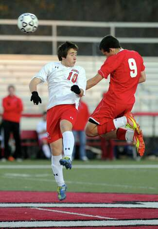 Fairfield Prep's Austin Sims and Greenwich's Julio Arnao jump to head the ball during Friday's Class LL boys soccer semifinal game at New Canaan High School on November 16, 2012. Photo: Lindsay Niegelberg / Stamford Advocate