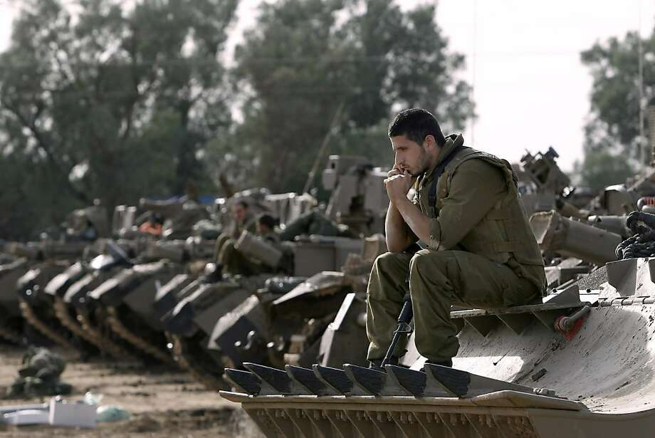 Israeli soldiers with armored vehicles gather in a staging ground near the border with Gaza Strip, southern Israel, Friday, Nov. 16, 2012. Fierce clashes between Israeli forces and Gaza militants are continuing for the third day. Photo: Tsafrir Abayov, Associated Press