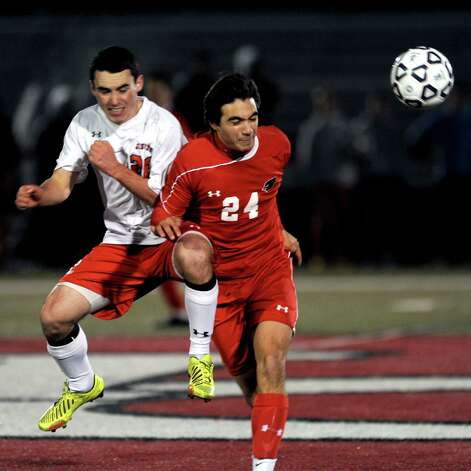 Fairfield Prep's Nick Dosky and Greenwich's Erik Thakor jump to head the ball during Friday's Class LL boys soccer semifinal game at New Canaan High School on November 16, 2012. Photo: Lindsay Niegelberg / Stamford Advocate