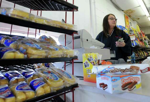 Wonder Bread Bakery Outlet clerk Candee Sollami rings out a steady flow of customers at the store on Wells Street in Bridgeport, Conn. on Friday, Nov. 16, 2012. Nearly 200 Connecticut workers face losing their jobs after Hostess Brands Inc. announced itâÄôs going out of business. The closing would mean the loss of about 18,500 jobs. Hostess employs about 200 workers in Connecticut in non-bakery retail and distribution facilities. The 50 employees in Bridgeport are caught in a fight between management and The Bakery Confectionery, Tobacco Workers and Grain Millers International Union, which went on strike last week over benefits and the future of the company. Teamsters Local 145, represents Hostess drivers, mechanics and thrift store employees at its the Bridgeport facility. Photo: Cathy Zuraw / Connecticut Post