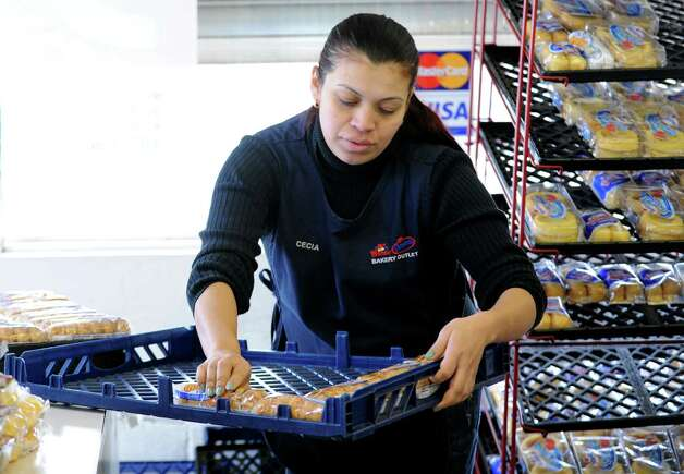 Wonder Bread Bakery Outlet clerk Cecia Villatoro stocks the shelves at the store on Wells Street in Bridgeport, Conn. on Friday, Nov. 16, 2012. Nearly 200 Connecticut workers face losing their jobs after Hostess Brands Inc. announced itâÄôs going out of business. Hostess employs about 200 workers in Connecticut in non-bakery retail and distribution facilities. The 50 employees in Bridgeport are caught in a fight between management and The Bakery Confectionery, Tobacco Workers and Grain Millers International Union, which went on strike last week over benefits and the future of the company. Teamsters Local 145, represents Hostess drivers, mechanics and thrift store employees at its the Bridgeport facility. Photo: Cathy Zuraw / Connecticut Post