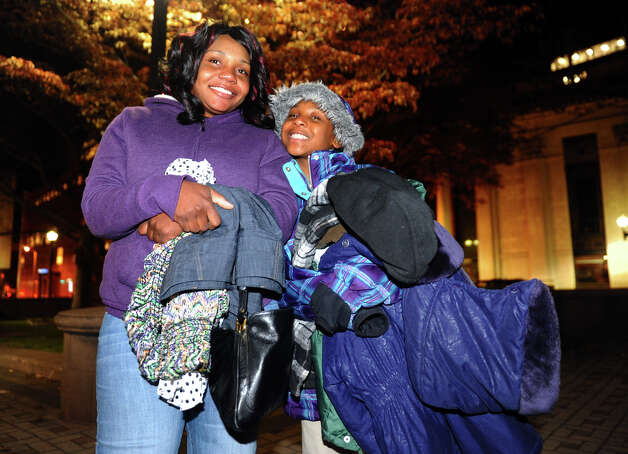 Residents Nikeisha Griffiths and her daughter Cobe, 10, leave with plenty of warm cloths given out during an event on McLevy Green to help the city's homeless and needy in downtown Bridgeport, Conn. on Friday November 16, 2012. It was hosted by A Better Bridgeport. Bread and blankets supplied by the organization Helping Hands in the Community were given out as well as donated clothing. Photo: Christian Abraham / Connecticut Post