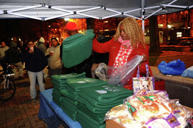 Volunteer Arlene Mercer puts blankets out at the start of an event on McLevy Green to help the city's homeless and needy in downtown Bridgeport, Conn. on Friday November 16, 2012. It was hosted by A Better Bridgeport. Bread and blankets supplied by the organization Helping Hands in the Community were given out as well as donated clothing. Photo: Christian Abraham / Connecticut Post