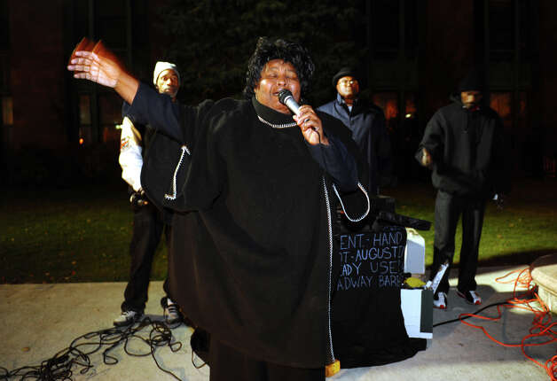 Volunteer Gloria Brown prays at the start of an event on McLevy Green to help the city's homeless and needy in downtown Bridgeport, Conn. on Friday November 16, 2012. It was hosted by A Better Bridgeport. Bread and blankets supplied by the organization Helping Hands in the Community were given out as well as donated clothing. Photo: Christian Abraham / Connecticut Post