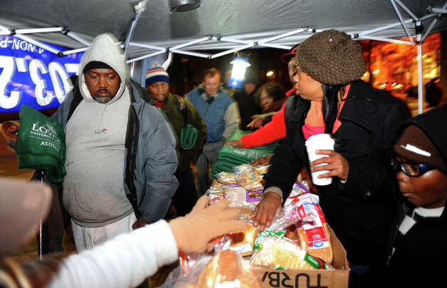 Volunteers give out warm blankets and bread during an event on McLevy Green to help the city's homeless and needy in downtown Bridgeport, Conn. on Friday November 16, 2012. It was hosted by A Better Bridgeport. The bread and blankets were supplied by the organization Helping Hands in the Community as well as donated clothing. Photo: Christian Abraham / Connecticut Post