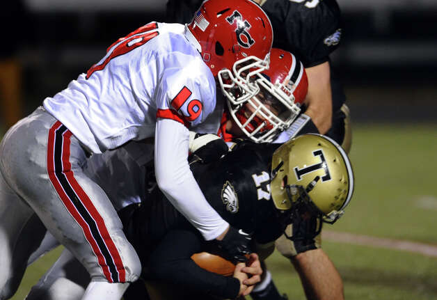 New Canaan's #19 John Rhudy and another player sack Trumbull QB Nick Roberts, during boys football action in Trumbull, Conn. on Friday November 16, 2012. Photo: Christian Abraham / Connecticut Post