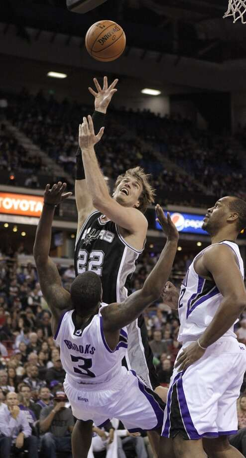 Spurs forward Tiago Splitter (center) charges into Kings guard Aaron Brooks as Kings forward Chuck Hayes (right) looks on during the first quarter in Sacramento, Calif., Friday, Nov. 9, 2012.
