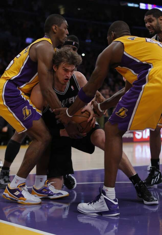 The Spurs' Tiago Splitter (center) gets a rebound against the Lakers' Metta World Peace (left) and Antawn Jamison in the second half in Los Angeles, Tuesday, Nov. 13, 2012. The Spurs won 84-82.