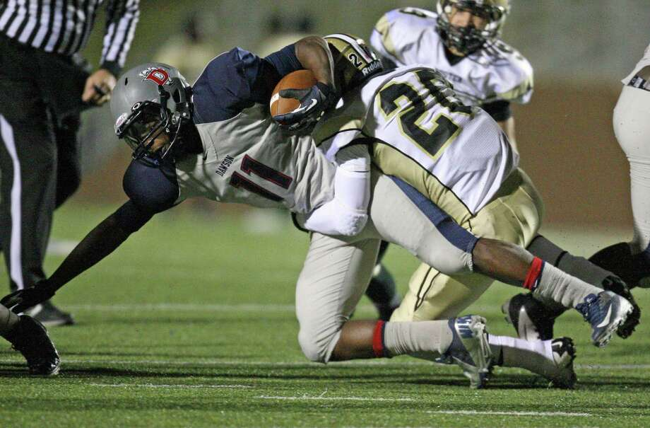 Dawson's Tony Upchurch (11) fights for extra yardage while being tackled by Foster's Lionel Egbe during the first half of a Class 4A Division I high school football playoff game, Friday, November 16, 2012 at Galena Park ISD Stadium. Photo: Eric Christian Smith, For The Chronicle