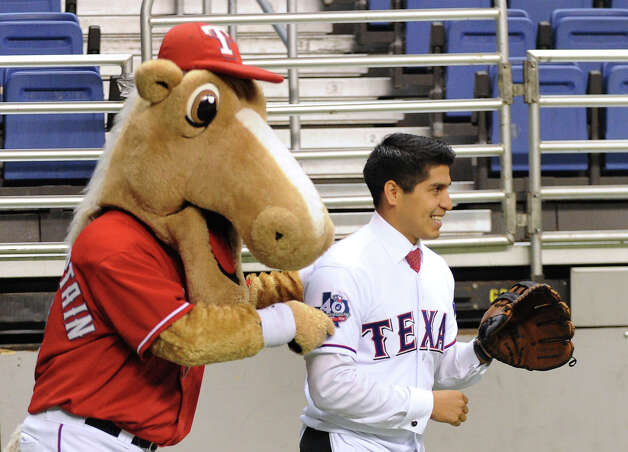 """Rangers Captain,"" mascot of the Texas Rangers, pesters San Antonio City Councilman Rey Saldana, who prepares to catch the first pitch during a press conference on Friday, Nov. 16, 2012, to announce ""Big League Weekend,"" a two-game set between the Texas Rangers and the San Diego Padres to be played in the Alamodome on March 29-30, 2013. Photo: Billy Calzada, Express-News / © 2012 San Antonio Express-News"