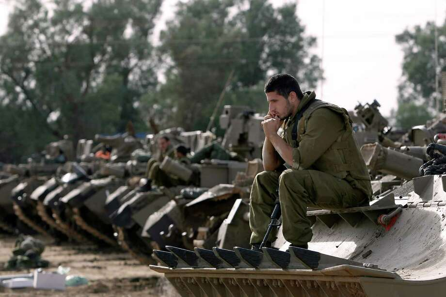 Israeli soldiers with armored vehicles gather in a staging ground near the border with Gaza Strip, southern Israel, Friday, Nov. 16, 2012. Fierce clashes between Israeli forces and Gaza militants are continuing for the third day.(AP Photo/Tsafrir Abayov) Photo: Tsafrir Abayov