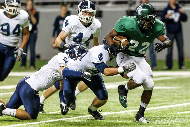 Reagan's Elijah Ball (right) runs through a tackle by Smithson Valley's Mason Nasis (center) and Clayton Lauderdale en route to a second quarter touchdown during their Class 5A Division II first round game at the Alamodome on Nov 16, 2012.  Smithson Valley won the game 21-14.  MARVIN PFEIFFER/ mpfeiffer@express-news.net Photo: MARVIN PFEIFFER, Express-News / Express-News 2012