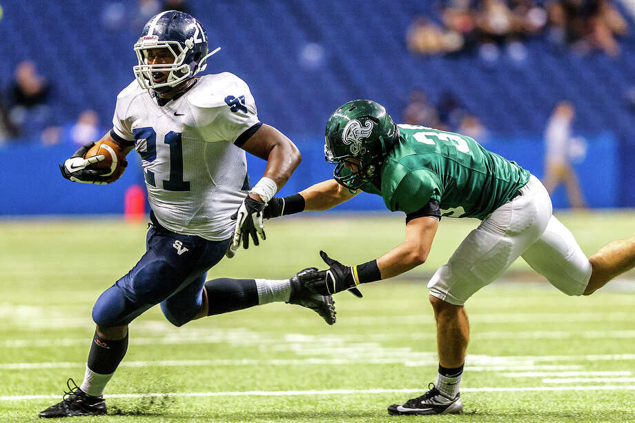Smithson Valley's Lawrence Mattison (left) avoids a tackle by Reagan's Jacob Killeen during the fourth quarter of their Class 5A Division II first round game at the Alamodome on Nov 16, 2012.  Smithson Valley won the game 21-14.  MARVIN PFEIFFER/ mpfeiffer@express-news.net Photo: MARVIN PFEIFFER, Express-News / Express-News 2012