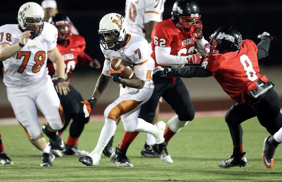 Madison's Marquis Warford (07) streaks past the grip of Wagner's Chiante Rome (08) on his way to a touchdown in the Class 5A District I playoff game in the second half at Rutledge Stadium on Friday, Nov. 16, 2012. Madison moves on with a 37-21 win over Wagner. Photo: Kin Man Hui, Express-News / © 2012 San Antonio Express-News