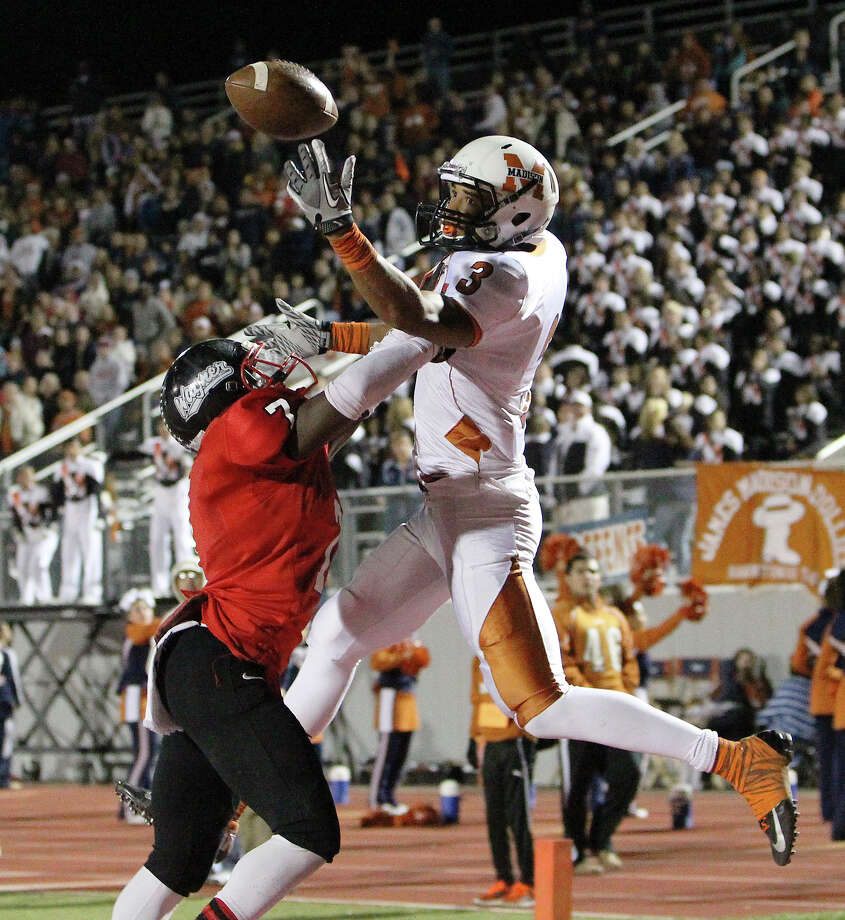 Madison's Dannon Cavil  (03) manages a finger grab for a touchdown against Wagner's Robert Gardner (07) in the Class 5A District I playoff game in the second half at Rutledge Stadium on Friday, Nov. 16, 2012. Madison moves on with a 37-21 win over Wagner. Photo: Kin Man Hui, Express-News / © 2012 San Antonio Express-News