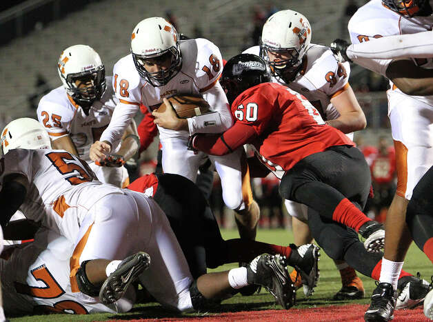 Madison quarterback Tyler Mangold (18) plunges in for a touchdown against Wagner's Jaden Moore (60) in the Class 5A District I playoff game in the second half at Rutledge Stadium on Friday, Nov. 16, 2012. Madison moves on with a 37-21 win over Wagner. Photo: Kin Man Hui, Express-News / © 2012 San Antonio Express-News