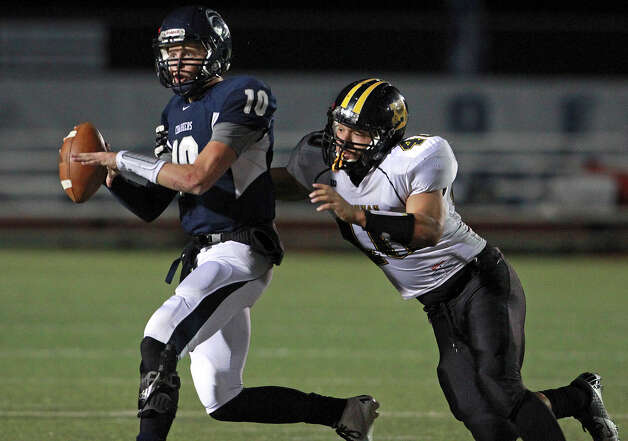 With Troy Irby moving in, Charger quarterback Kyle Poeske looks for a receiver as Champion hosts Brennan in 4A first round playoff action at Boerne Stadium on November 16, 2012. Photo: Tom Reel, Express-News / ©2012 San Antono Express-News