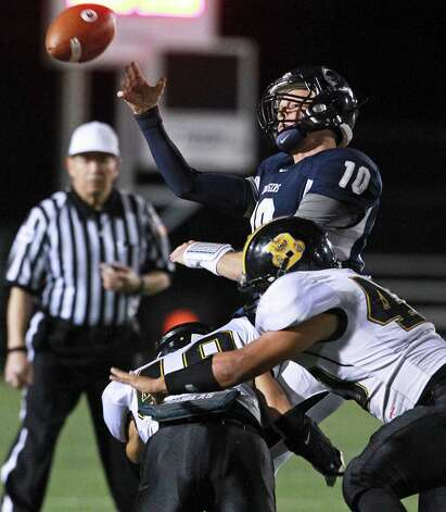 Charger quarterback Kyle Poeske is pressured to make a bad throw by Michael Huron (49) and Troy Irby as Champion hosts Brennan in 4A first round playoff action at Boerne Stadium on November 16, 2012. Photo: Tom Reel, Express-News / ©2012 San Antono Express-News