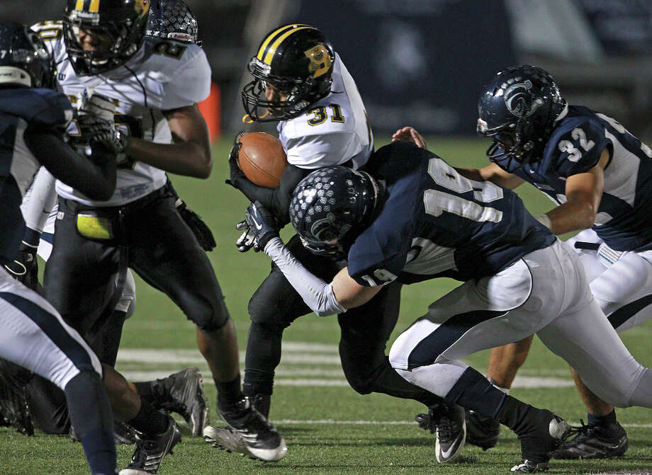 Bears running back Makai Green is stopped by Jake Margozewitz as Champion hosts Brennan in 4A first round playoff action at Boerne Stadium on November 16, 2012. Photo: Tom Reel, Express-News / ©2012 San Antono Express-News