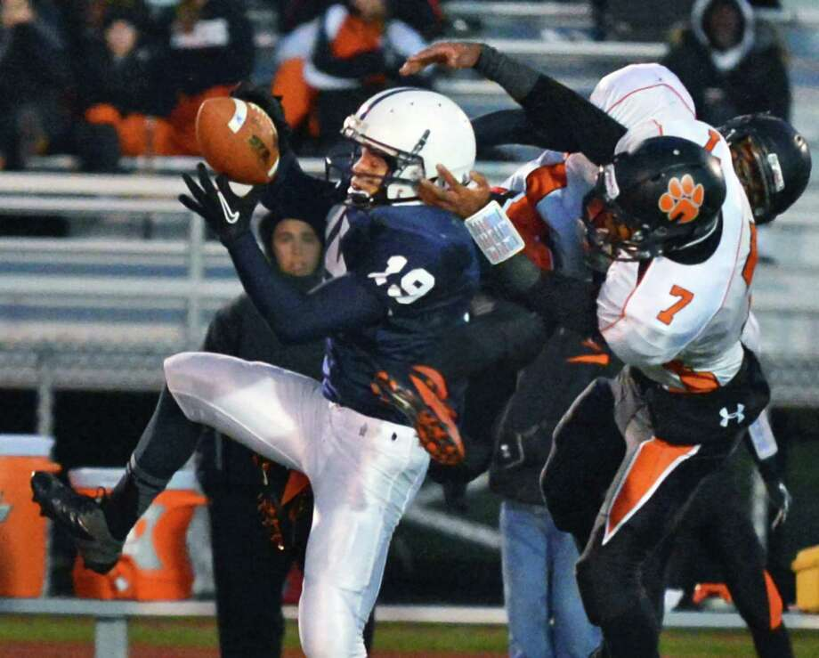 Rensselaer's #19 Brandon Butler reels in a pass from QB Steven Harwood despite two Tuckahoe defenders during the Class D semifinal game at Dietz Stadium in Kingston Friday Nov. 16, 2012.  (John Carl D'Annibale / Times Union) Photo: John Carl D'Annibale / 00020085A