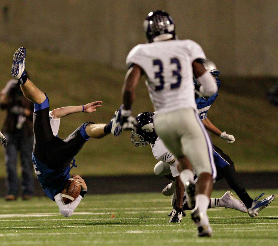 Friendswood quarterback Jordan Wood gets tripped up during a high school football game between Angleton and Friendswood in a Class 4A Division 1 playoffs at Hall Stadium on November 16, 2012. Angleton won 48-41. Photo: Bob Levey, Houston Chronicle / ©2012 Bob Levey