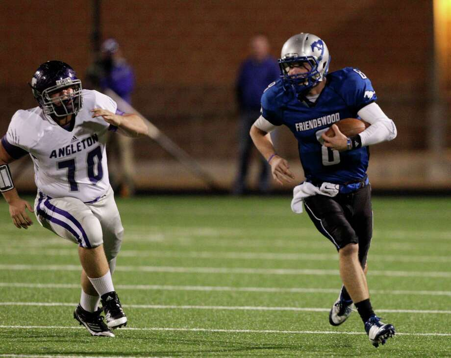Friendswood quarterback Jordan Wood rushes as he is pursued by Angleton's Justin Bell during a high school football game between Angleton and Friendswood in a Class 4A Division 1 playoffs at Hall Stadium on November 16, 2012.Angleton won 48-41. Photo: Bob Levey, Houston Chronicle / ©2012 Bob Levey