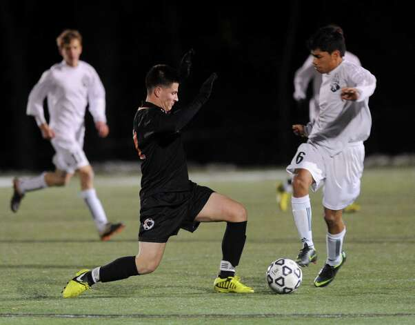 Stamford's Steven Lopez and Norwalk's Jose Canahui compete for control of the ball during Friday's Class LL boys soccer semifinal game at New Canaan High School on November 16, 2012. Photo: Lindsay Niegelberg / Stamford Advocate