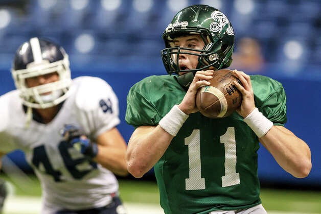 Reagan quarterback Kyle Keller looks for a receiver as he rolls out of the pocket with Smithson Valley's Mason Nasis in pursuit during the fourth quarter of their Class 5A Division II first round game at the Alamodome on Nov 16, 2012. Smithson Valley won the game 21-14.  MARVIN PFEIFFER/ mpfeiffer@express-news.net Photo: MARVIN PFEIFFER, Express-News / Express-News 2012