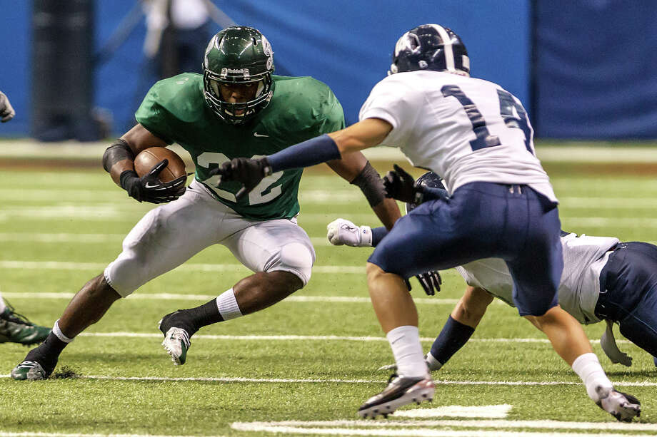 Reagan's Elijah Ball (left) looks for a way around Smithson Valley's Carlos Costello during the third quarter of their Class 5A Division II first round game at the Alamodome on Nov 16, 2012.  Smithson Valley won the game 21-14.  MARVIN PFEIFFER/ mpfeiffer@express-news.net Photo: MARVIN PFEIFFER, Express-News / Express-News 2012