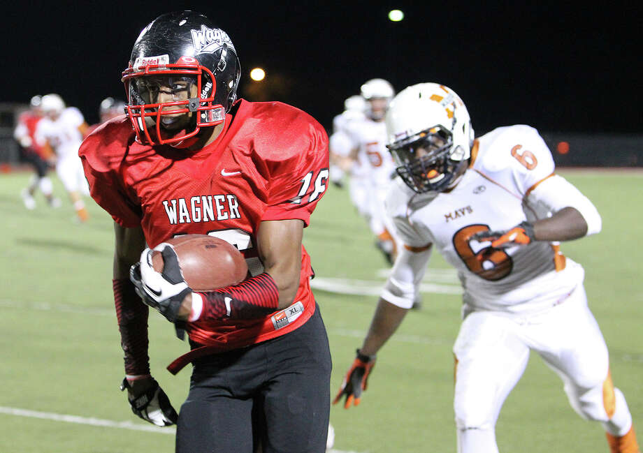 Wagner's Tremaine Allen (16) sprints away from Madison's Dominique Daniels (06) on his way to a touchdown in the Class 5A District I playoff game in the first half at Rutledge Stadium on Friday, Nov. 16, 2012. Photo: Kin Man Hui, Express-News / © 2012 San Antonio Express-News