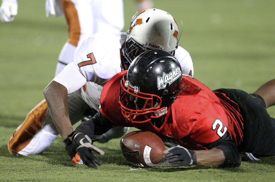 Wagner's Kenny Stewart (02) makes fumble recovery on a punt against Madison's Marquis Warford (07) in the Class 5A District I playoff game in the first half at Rutledge Stadium on Friday, Nov. 16, 2012. Photo: Kin Man Hui, Express-News / © 2012 San Antonio Express-News