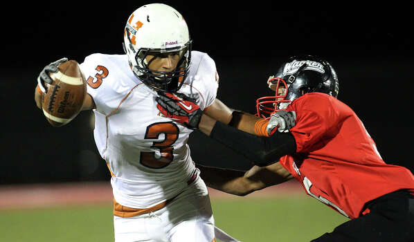 Madison's Dannon Cavil (03) fends off Wagner's Jacorey Walker (05) after a pass reception in the Class 5A District I playoff game in the second half at Rutledge Stadium on Friday, Nov. 16, 2012. Madison moves on with a 37-21 win over Wagner. Photo: Kin Man Hui, Express-News / © 2012 San Antonio Express-News