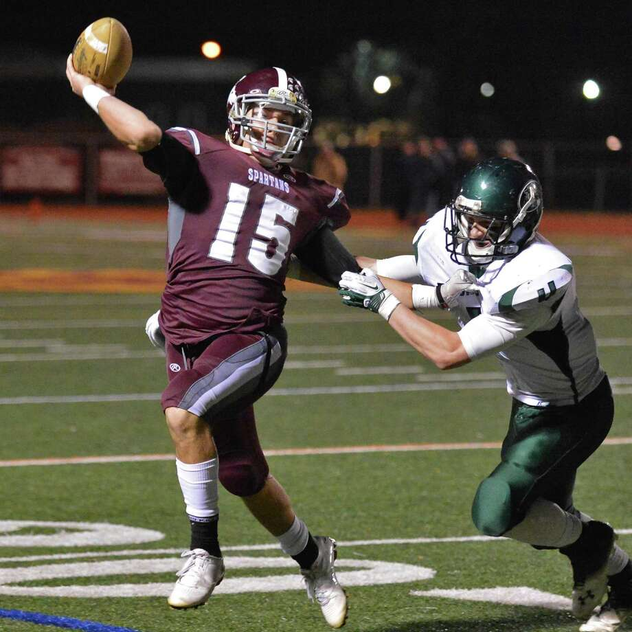 Burnt Hills quarterback Ryan McDonnell fires off a touchdown pass to Matthew Peltier as Cornwall's #4 Jeff Grygiel closes in during the Class A semifinal at Dietz Stadium in Kingston Friday Nov. 16, 2012.  (John Carl D'Annibale / Times Union) Photo: John Carl D'Annibale / 00020084A