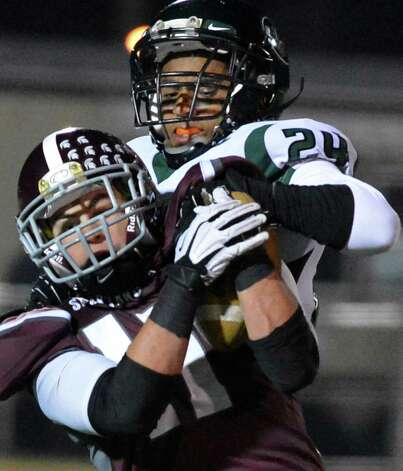 Burnt Hills #11 Daniel Maynard, left, fights off a tackle by Cornwall's # 24 Anthony Vega during the Class A semifinal at Dietz Stadium in Kingston Friday Nov. 16, 2012.  (John Carl D'Annibale / Times Union) Photo: John Carl D'Annibale / 00020084A