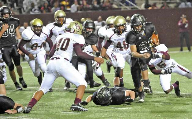 Pirate #23, Montana Quirante, right, runs through a line of Bulldog defenders. The Vidor High School Pirates football team played the Humble Summer Creek Bulldogs at 7 p.m. Friday night at Clyde Abshier Stadium in Deer Park Texas. This is a Class 4A Division I first round game.  At the half, Humble Summer Creek was ahead 24-14. Dave Ryan/The Enterprise Photo: Dave Ryan