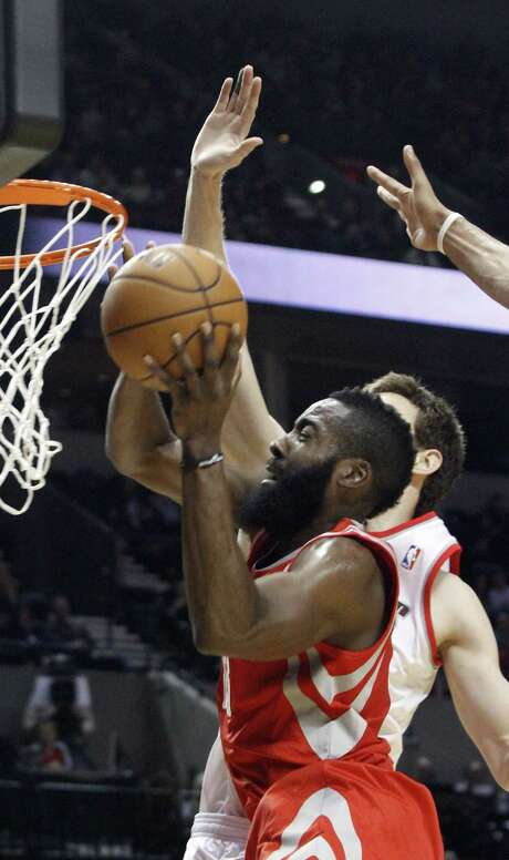 Rockets guard James Harden, left, goes to the hoop despite the efforts of Trail Blazers forward Victor Claver during first-half action Friday night. Photo: Don Ryan, STF / AP